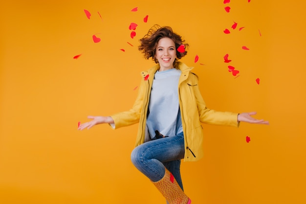 노란색 벽에 점프하는 동안 마음을 던지고 세련 된 갈색 머리 소녀. 발렌타인 데이에 재미 재킷에 꽤 유럽 젊은 여자.