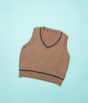 Стильный коричневый вязаный жилет на синем фоне. модная классическая вязаная одежда.
