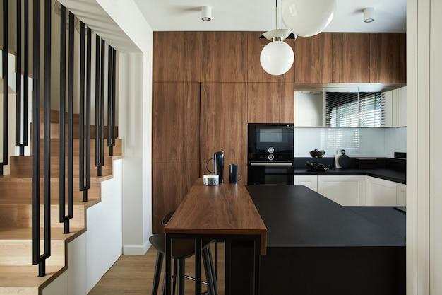 빌트인 주방과 주방 아일랜드, 개인용 액세서리가 있는 세련된 브라운 패널 주방 인테리어. 기하학적 형태와 모양. 주형.