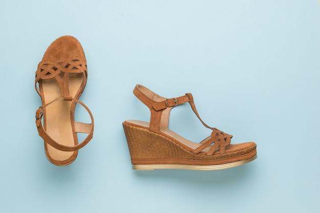 Stylish brown women's suede sandals on a blue background. summer shoes for women. flat lay.