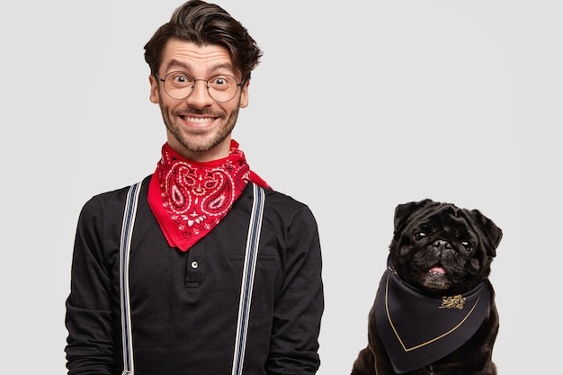 Stylish brunet man wearing red bandana next to dog