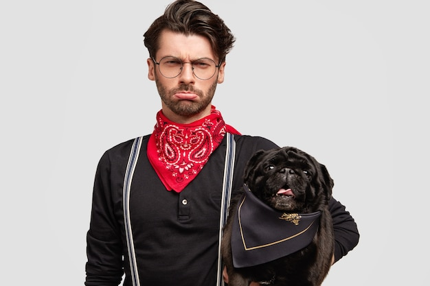 Stylish brunet man wearing red bandana holding dog