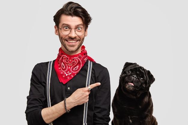 犬の横にある赤いバンダナを身に着けているスタイリッシュな黒髪の男