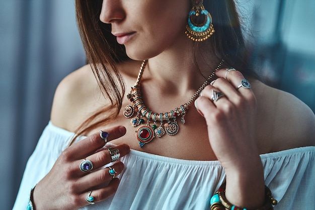 Stylish brunette boho woman wearing white blouse with big earrings, necklace with stone and silver rings. fashionable indian hippie gypsy bohemian outfit with imitation jewelry details