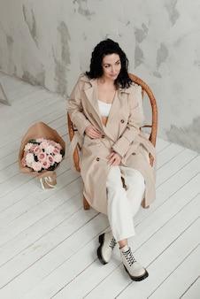 베이지 색 긴 트렌치 코트 흰색 바지와 큰 부츠에 세련된 갈색 머리 소녀는 꽃의 큰 꽃다발 옆에 의자에 앉아