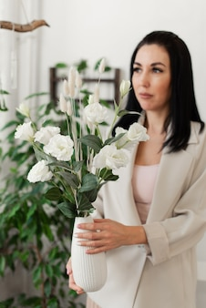 꽃의 꽃병을 들고 가벼운 재킷에 세련된 갈색 머리 소녀