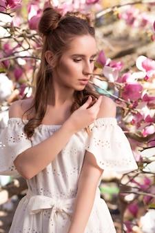 흰색 레이스 드레스를 입고 꽃이 만발한 목련 나무 근처에서 포즈를 취하는 세련된 갈색 머리 소녀