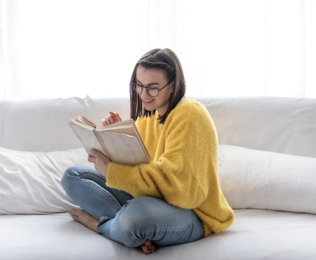 Elegante ragazza bruna in un maglione giallo e occhiali legge un libro a casa sul divano. il concetto di autosviluppo e rilassamento.