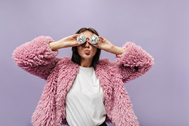 Stylish brunette haired lady in plain t-shirt and long sleeve pink trendy sweater holding two small disco balls on lilac wall
