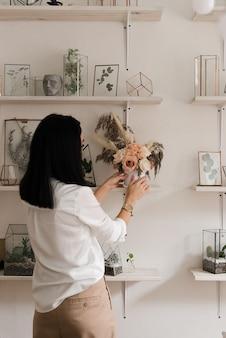 白いシャツのスタイリッシュなブルネットは、棚の上の花瓶で部屋を飾ります