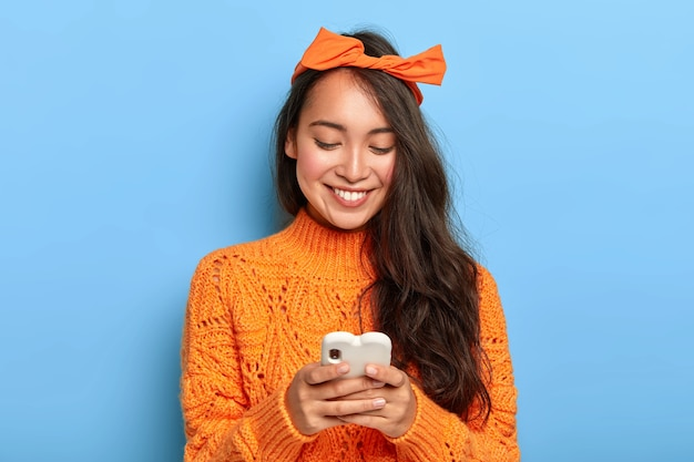 Stylish brunette millennial girl busy checking her email box, holds mobile phone, wears orange headband tied in bow, warm sweater