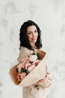 공예 종이에 꽃의 큰 꽃다발을 들고 베이지 색 트렌치 코트에 세련된 갈색 머리 모델