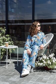 새로운 옷 컬렉션에서 의자에 앉아 포즈를 취하는 세련된 갈색 머리 모델