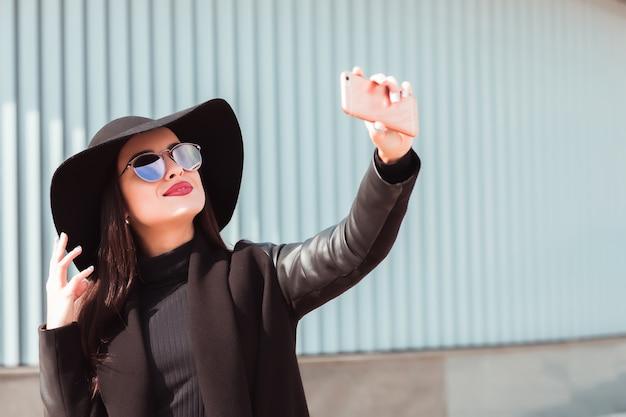 スタイリッシュなブルネットのモデルは、携帯電話で自分撮りをして、ファッショナブルな帽子とサングラスを身に着けています
