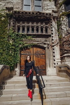 Stylish brunette standing next to the entance to a building