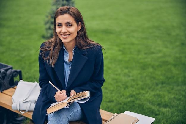 벤치에 앉아 웃고있는 동안 밖에서 공부하는 세련된 갈색 머리 학생 여성