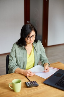 Stylish brunette woman in glasses sitting at wooden table with notepad working in her office