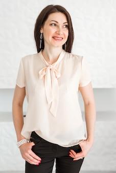 Стильная брюнетка в легкой блузке, держит руки в карманах, позирует у светлой стены и смотрит в сторону.