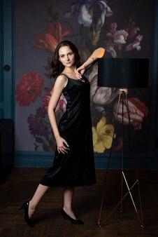 ランプとデザイナースタジオでポーズをとって黒い絹のドレスのスタイリッシュなブルネットの女性