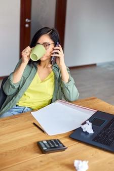 メモ帳と電話を持っている木製のテーブルに座ってメガネでスタイリッシュなブルネットの女性
