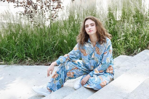 도시 거리에 있는 새로운 옷 컬렉션의 계단에 앉아 포즈를 취하는 세련된 브루네트 여성 모델
