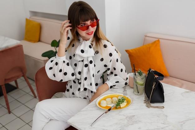 スタイリッシュなブルネットの女性のカフェに座って、カクテルを飲む