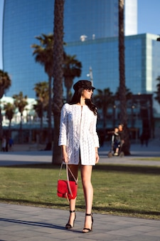 Stylish brunette woman walking , fancy luxury style outfit, modern buildings and palms, toned colors.