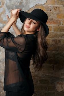 グランジの壁の近くでポーズをとって帽子と黒のブラウスを身に着けているスタイリッシュなブルネットの女性