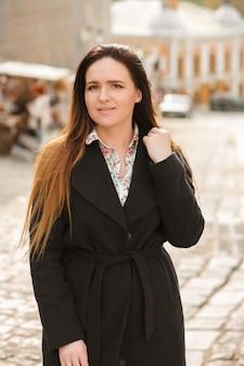コートを着て、通りでポーズをとって長い髪のスタイリッシュなブルネットの女性
