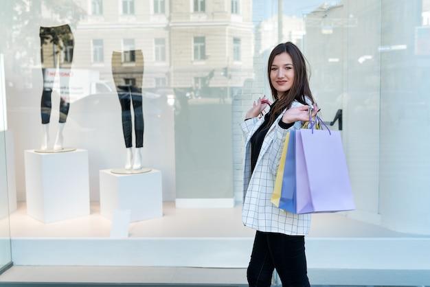 ショーケースの背景にマルチカラーのショッピングバッグを持つスタイリッシュなブルネットの女性。モックアップ。