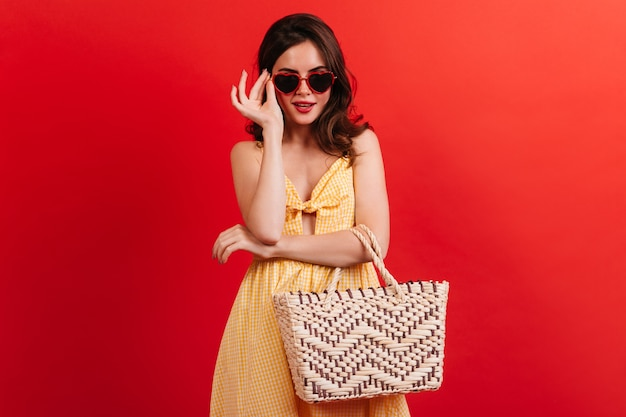 Stylish brunette in yellow sundress puts on glasses in shape of hearts. girl with beach bag posing on red wall.