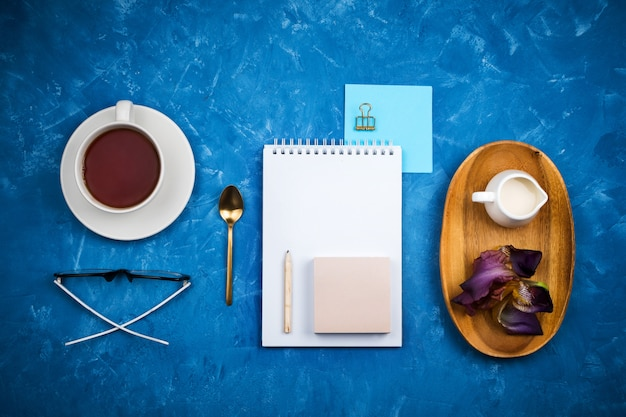 Stylish business flatlay mockup with knolled cup of black tea, notebook, glasses and pencil, milk holder on wooden tray on blue cement background