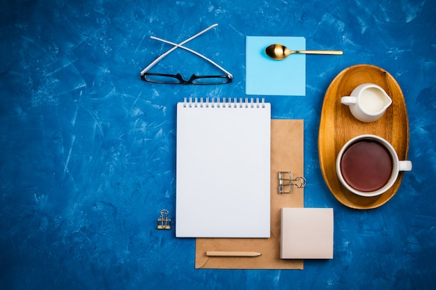 Stylish business flatlay mockup with notebook, glasses, pencil, milk holder and tea on wooden tray knolled together on blue cement background