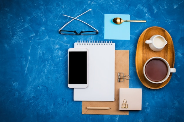 Stylish business flatlay mockup with notebook, glasses, pencil, milk holder and tea on wooden tray and smartphone with black copyspace knolled together on blue cement background