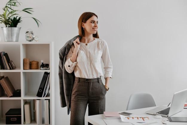 그녀의 사무실에서 포즈를 취하는 높은 영혼에 세련 된 비즈니스 여자. 짧은 머리를 가진 아가씨는 미소로 옆으로 보입니다.