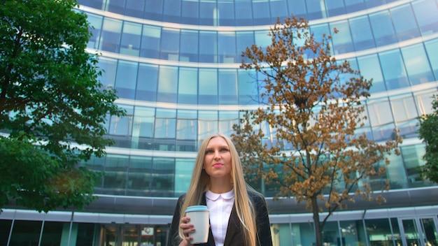 Стильная деловая женщина с кофе на улице снизу серьезной белокурой исполнительной девушки в костюме, пьющей кофе в бумажном стаканчике, глядя на улицу