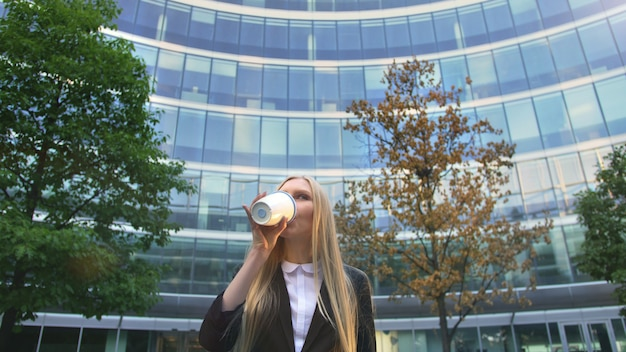 通りでコーヒーを飲みながらスタイリッシュなビジネス女性