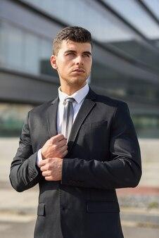 Стильный бизнесмен фиксируя его костюм