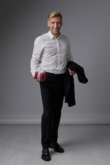 Stylish businessman holding gift box