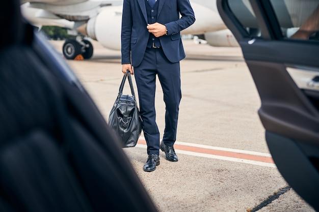 出張に行く車に向かって歩いてスタイリッシュに見えるスタイリッシュなビジネスマン