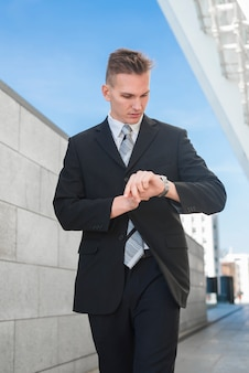 Stylish businessman looking at watch