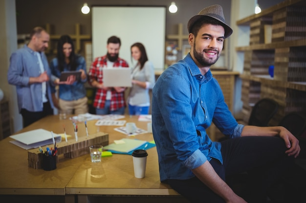 Stylish businessman sitting on table in creative office
