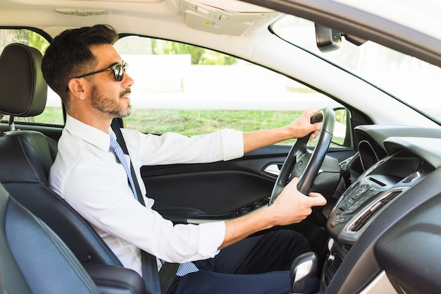Stylish businessman wearing sunglasses driving the car