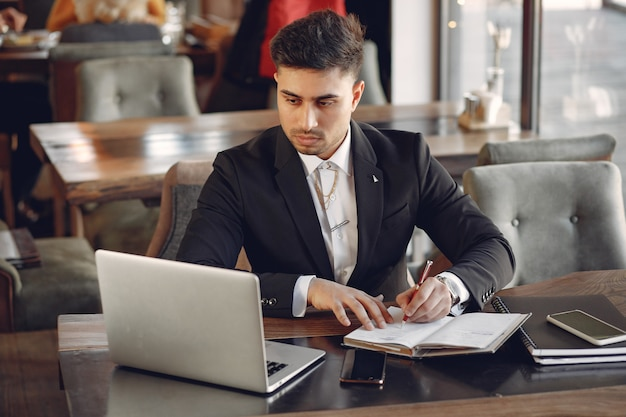Stylish businessman working in a cafe and use the laptop