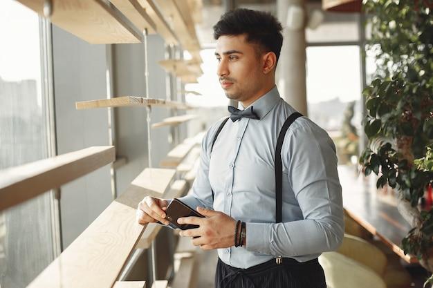 Стильный бизнесмен работает в офисе и пользоваться телефоном
