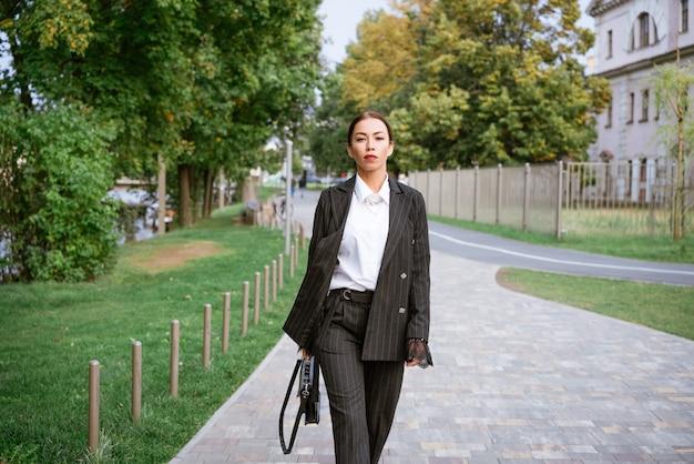 세련된 사업가, 그녀의 손에 양복과 셔츠와 가방에 거리에서 포즈를 취하는 아름다운 화장과 갈색 머리 백인 민족