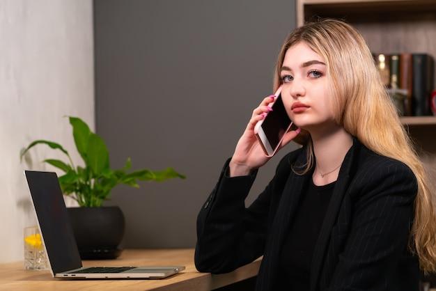 Стильная бизнес-леди разговаривает по мобильному телефону в офисе, сидя за своей лампой, поворачиваясь, чтобы взглянуть в камеру с серьезным выражением лица