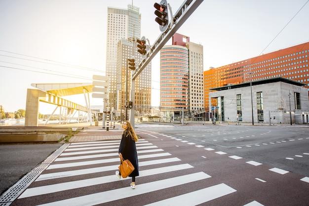 ロッテルダム市の朝の間に近代的な地区で通りを横断するスタイリッシュな実業家