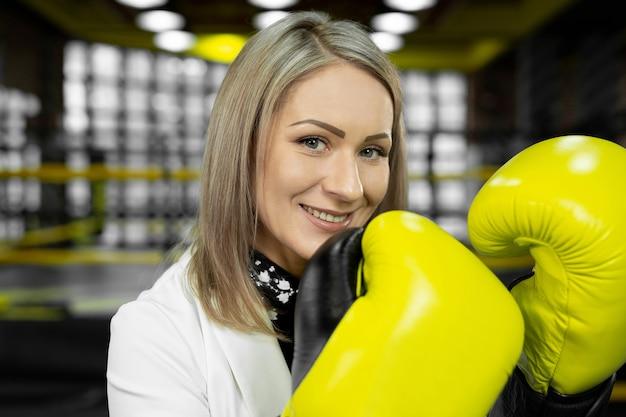 Стильная бизнес-леди в желтых боксерских перчатках на фоне боксерского ринга смотрит в камеру и смеется.