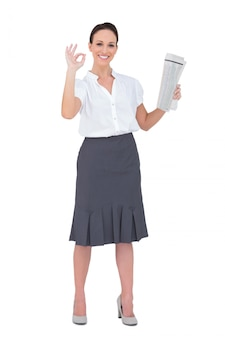 Stylish businesswoman making gesture while holding newspaper